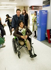Mauricio Quiroga pushes Estefania Salinas in her wheelchair as she arrives at Logan International Airport Feb. 27, 2014. Photo by Gregory L. Tracy